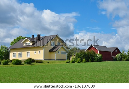 Wooden house and farm buildings in the countryside. Sunny summer day - stock photo