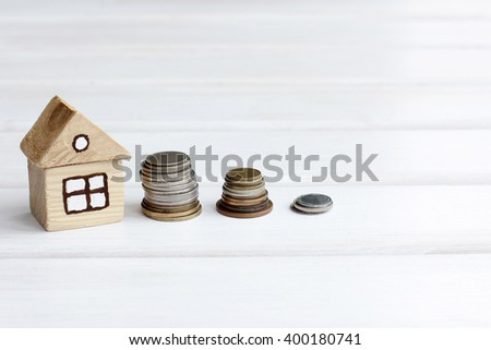 wooden house and stacks of coins standing next/accumulation of funds for a new home