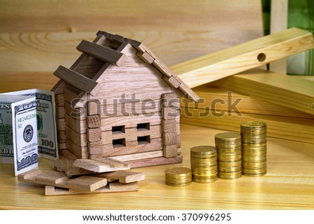 Wooden house block with coins. (finance, property and house loan concept). House miniature with pile of coins. Money for the building and details of the new building.