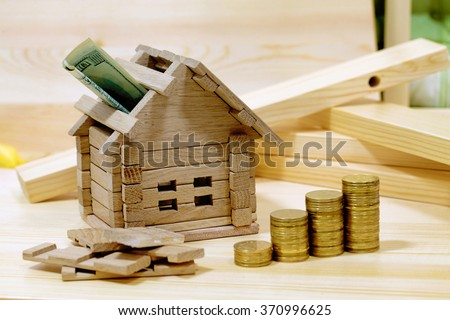Wooden house block with coins. (finance, property and house loan concept). Project cozy house. Money for the building and details of the new building.Buying a new home. - stock photo