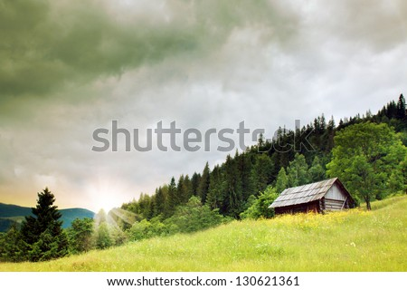 wooden house dramatic sunset in a mountains - stock photo