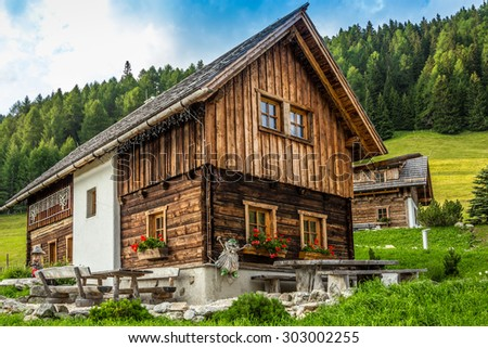 Wooden house, forest in background - stock photo