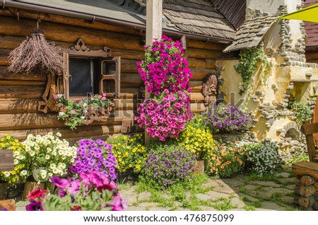 wooden house from logs decorated with bright and colorful petunia