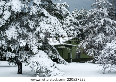 Wooden house in a nature area covered with freshly fallen snow - stock photo