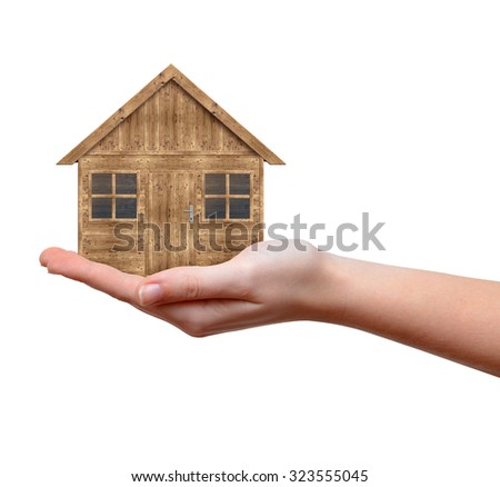 Wooden house in hand isolated on white background - stock photo