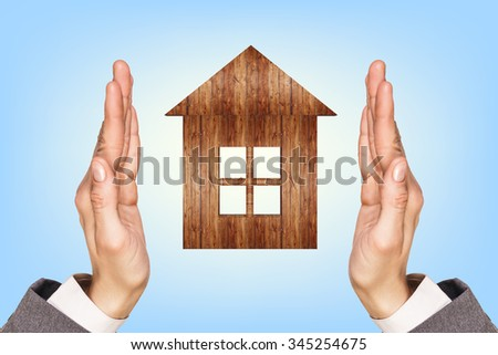 Wooden house in human hands over blue background - stock photo