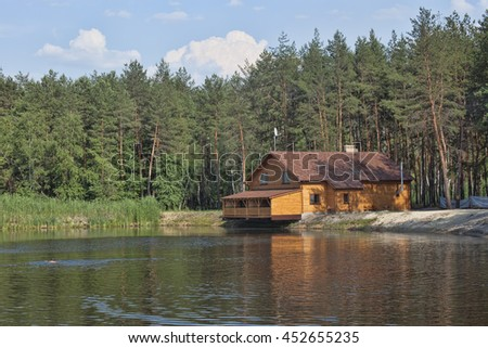 Wooden house in the forest above the lake