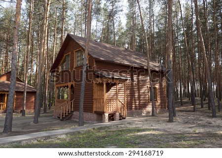 Wooden house in the forest between pine-tree