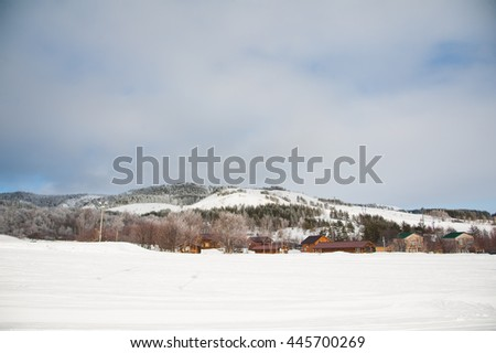 Wooden house in winter with lots of snow at the foot of the hill