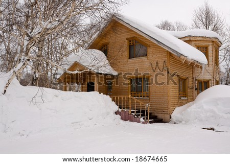 wooden house in winter wood fallen asleep by snow