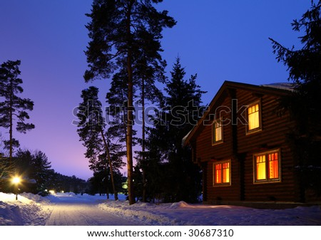 wooden house in winter wood in twilight - stock photo