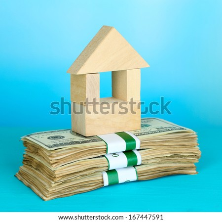 Wooden house on packs of dollars on blue background