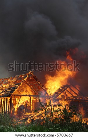 Wooden house on the huge fire - stock photo