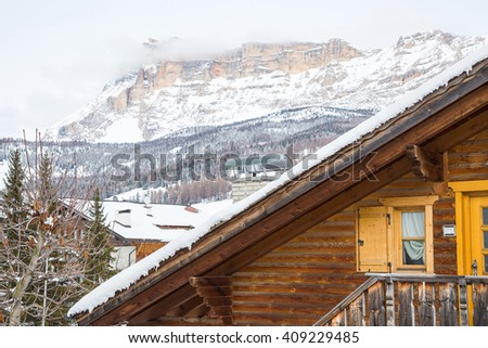 Wooden house standing in the mountains with snow on the roof in Italian Alps - stock photo