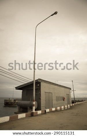 Wooden house store on small sea port in vintage tone - stock photo