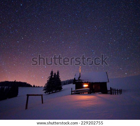 Wooden house with a light in the window. Night landscape in winter - stock photo