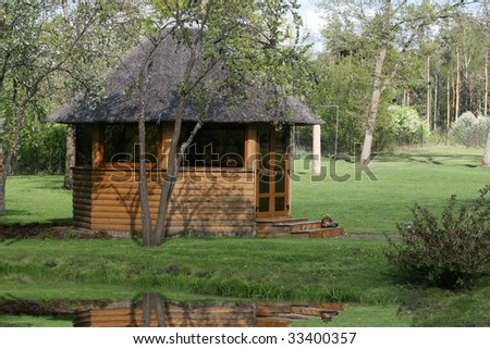 Wooden house with a straw roof on the bank of lake
