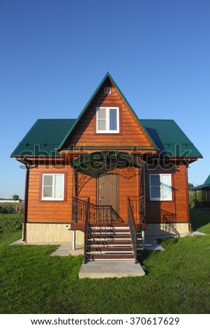 Wooden house with green metal roof fronton view photo