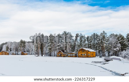 Wooden houses in a nature area covered with freshly fallen snow.  - stock photo