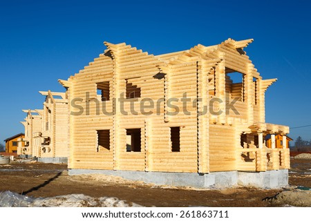 Wooden housing construction, felling from a round log  for sale - stock photo
