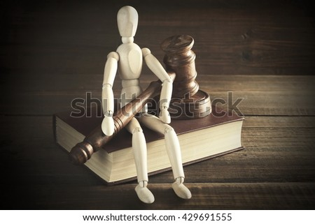 Wooden Human Figurine With  Judges Or  Auctioneer Gavel In Hand Sit On Red Book On The Rough And Grunge Wooden Table, Close Up, Front View, Effects - stock photo