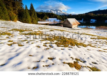 wooden hut on snow alpine meadow by lake, Geroldsee, Germany - stock photo