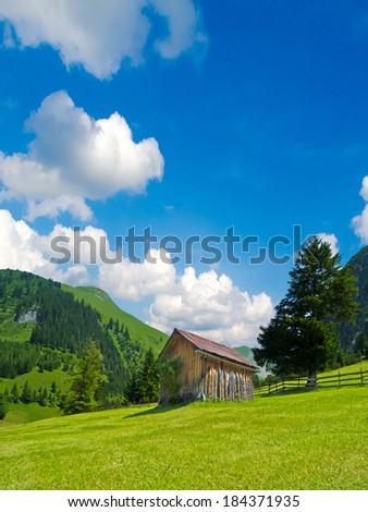 wooden hut surrounded by beautiful alpine landscape - stock photo