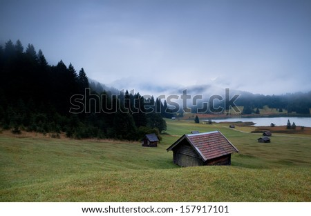 wooden huts and fog over Geroldsee lake in dusk, Bavarian Alps