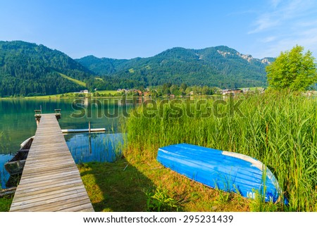 Wooden jetty and blue boat on shore of Weissensee alpine lake in summer landscape, Austria - stock photo