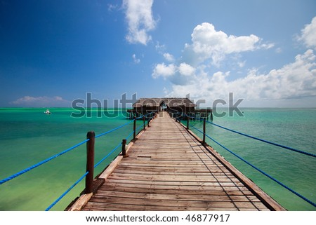 Wooden jetty and turquoise waters of tropical ocean - stock photo