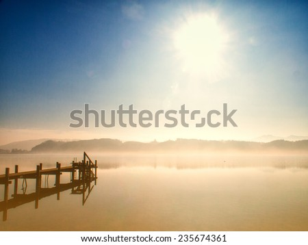 wooden jetty  at a little lake, foggy - stock photo