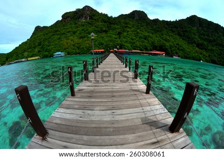 Wooden jetty headding towards the Bohey Dulang island. Sabah National Park Semporna. Image has grain or blurry or noise and soft focus when view at full resolution. (Shallow DOF, slight motion blur)  - stock photo