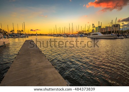 Wooden jetty in Ala Wai Harbor at sunset. Ala Wai Harbor is the largest small-boat and yacht harbor in Hawaii, situated between Waikiki and downtown Honolulu in Oahu Island, Hawaii, United States.