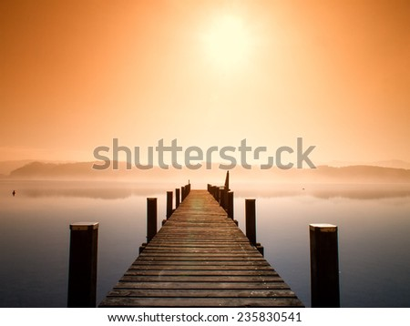 wooden jetty in morning fog - stock photo