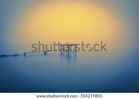 Wooden jetty in the autumn foggy river. - stock photo