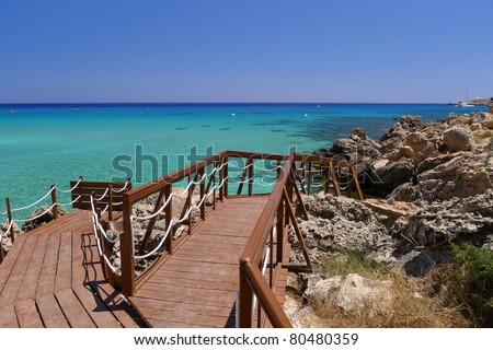 Wooden jetty leading to beautiful sea water of Konnos Bay on Cyprus island - stock photo
