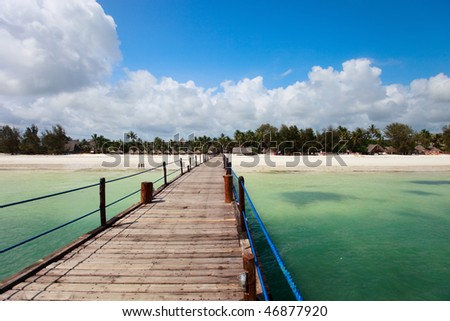Wooden jetty leading to exotic beach of tropical Zanzibar island - stock photo