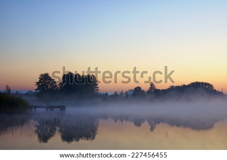Wooden jetty on calm foggy lake water surface just before sunrise, Mazury, Poland - stock photo