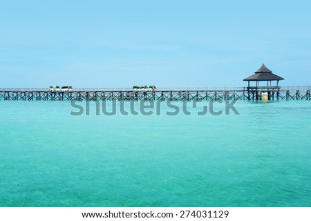 wooden jetty on clear water and blue sky - stock photo