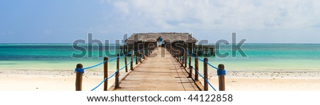 Wooden jetty on exotic beach of tropical Zanzibar island - stock photo