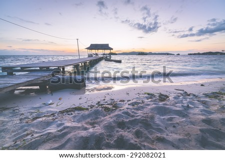Wooden jetty on the sea in tourist resort. Summer adventures on the remote Togian (Togean) Islands, Sulawesi, Indonesia. Wide angle shot at dawn, long exposure. Marsala toned image, vignetting added. - stock photo