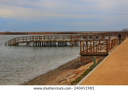 wooden jetty over a calm sea - stock photo
