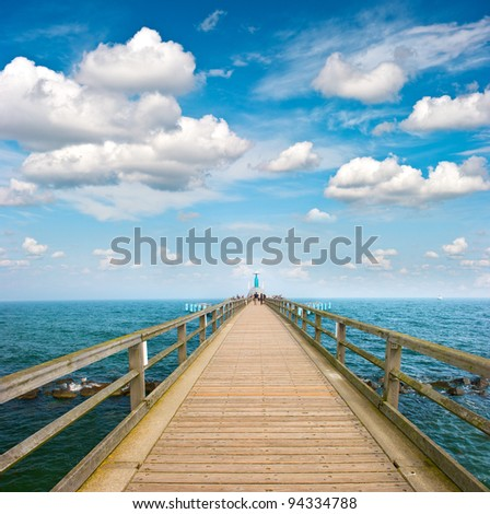 wooden jetty over sea. turquoise water and dramatic blue cloudy sky. Baltic Sea, Sellin, Germany