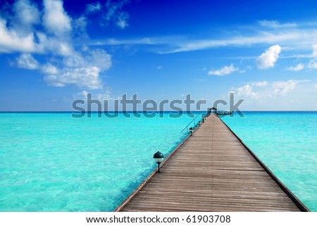 Wooden jetty over the beautiful Maldivian sea with blue sky - stock photo