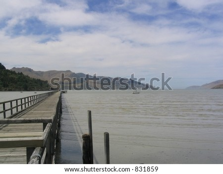 Wooden Jetty / pier running out in to a habour.  A town in the distance on the hillside.  (Lyttleton Harbour, New Zealand)