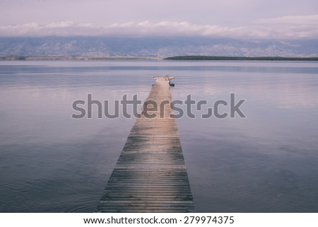 Wooden jetty surrounded by the water at the coast of Adriatic Sea - stock photo