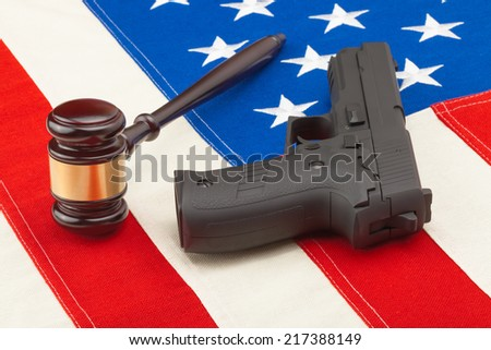Wooden judge gavel and gun over US flag - studio shot - stock photo
