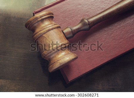 Wooden judge gavel and red legal book on wooden table - stock photo