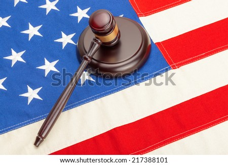 Wooden judge gavel and soundboard laying over US flag - stock photo