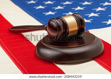 Wooden judge gavel and soundboard laying over USA flag - studio shoot - stock photo